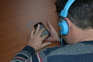 A blind person interacting with his smarptphone using over the ear headphones