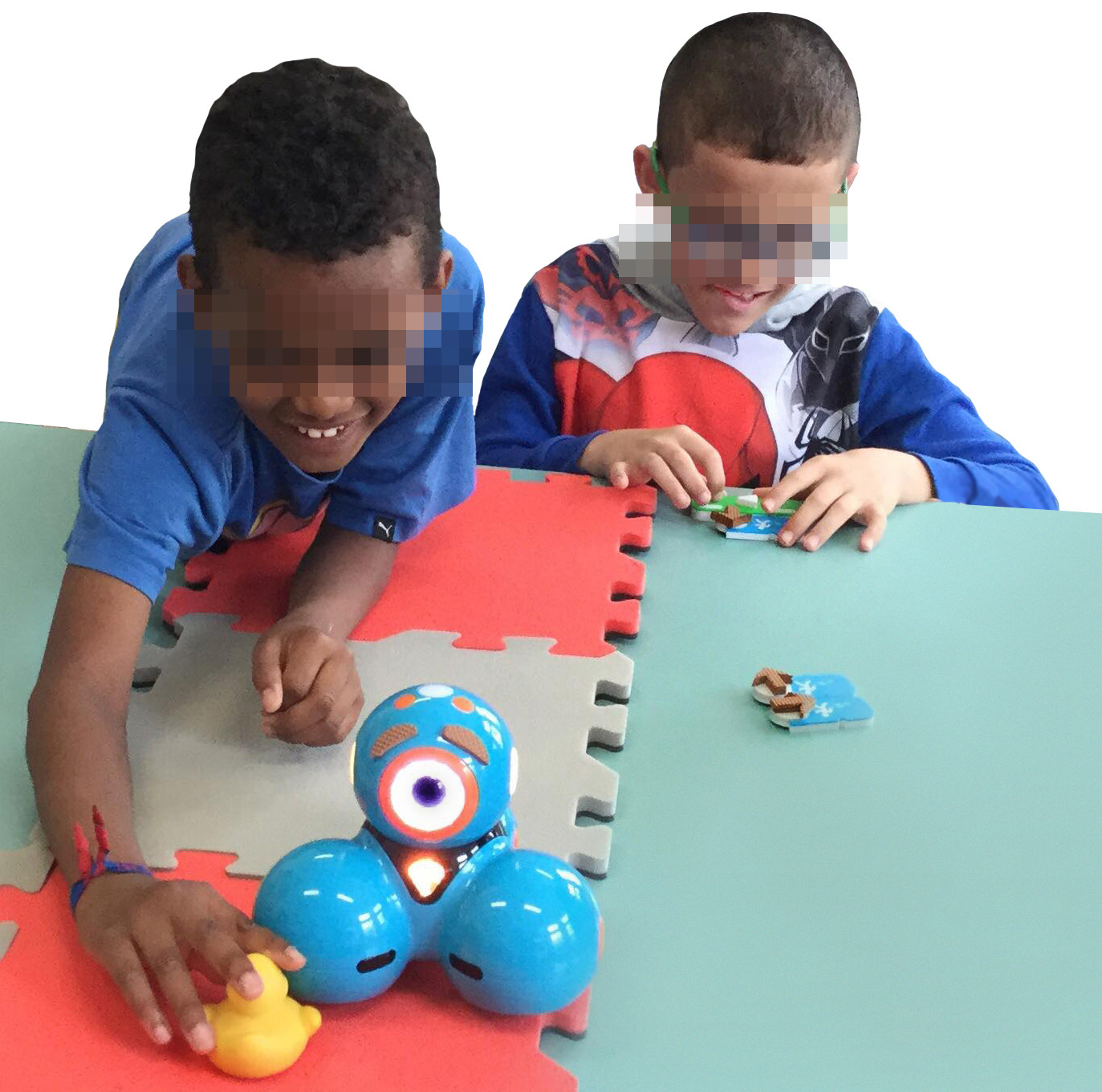 Photo taken from the Workshop with children. Two visually impaired children perform a goal-directed programming activity using a map located on the table. The activity consists of moving the robot to reach the duck. The map is made of 4 EVA foam tiles with two different colors. The child on the right is concentrated in arranging the blocks while the children at the left are touching the duck after the robot reached the duck. This child is smiling and has much of his body on the table.